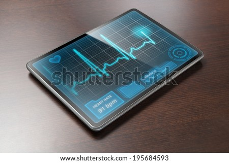 Medical tablet PC on table showing cardiogram on display - stock photo