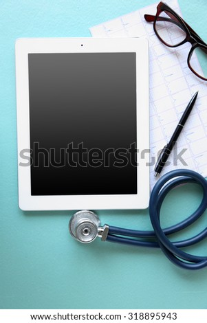 Medical tablet with screen empty screen on blue table - stock photo