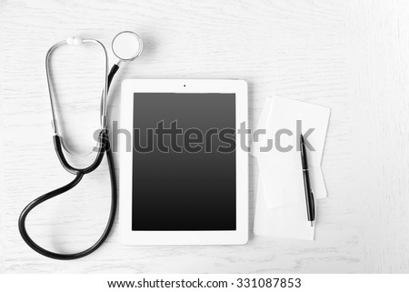 Medical tablet with screen empty screen on wooden table - stock photo