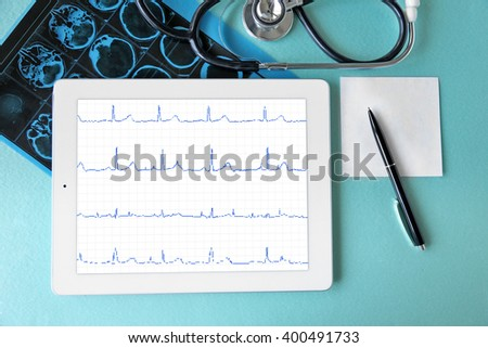 Medical tablet with stethoscope on blue background - stock photo