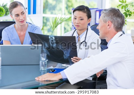 Medical team looking at x-ray during a meeting in the board room at the hospital - stock photo