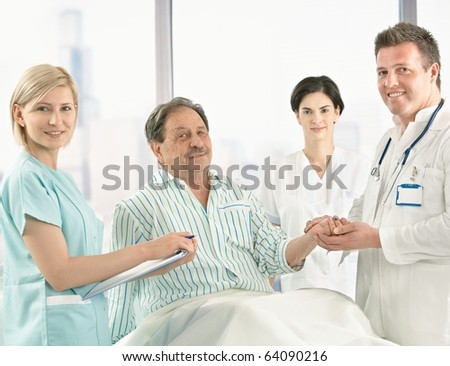 Medical team taking care of elderly patient sitting on hospital bed in pyjama, holding hands.? - stock photo