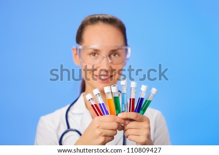Medical test tubes with fluid sample closeup in doctor hand on blue background - stock photo