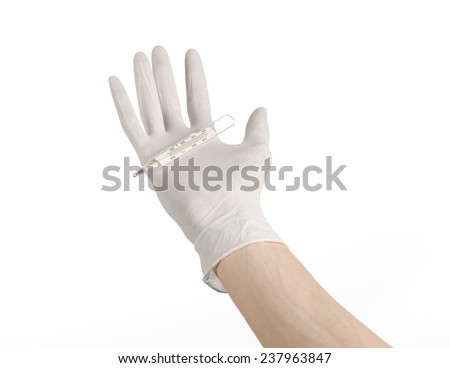 Medical theme: doctor's hand in white gloves holding a thermometer to measure the temperature of the patient on a white background - stock photo
