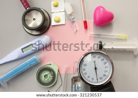 Medical theme -pill, syringe, needle, medical thermometer, heart, blood pressure equipment, surgical thread and stethoscope - copy space on grey background - stock photo