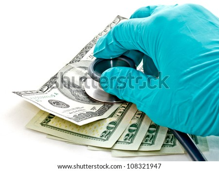 medical treatment and cost concept: doctor's hand hold stethoscope placing on US dollar banknotes - stock photo