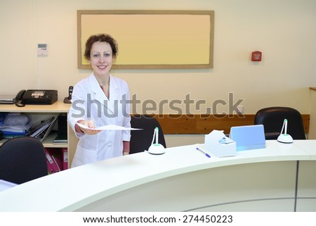 Medical worker in white coat holds out a sheet of paper at the reception - stock photo