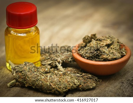 Medicinal cannabis with extracted oil in a bottle - stock photo