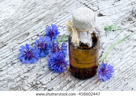 Medicinal plant Centaurea cyanus, commonly known as cornflower and pharmaceutical bottle on old wooden table - stock photo