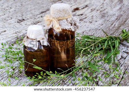 Medicinal plant shepherd's purse (Capsella bursa-pastoris) and brown pharmaceutical bottle on old wooden table. Used in herbal medicine, healthy eating, as well as for cosmetics purposes - stock photo