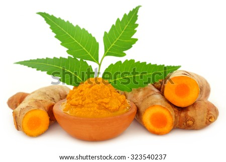 Medicinal turmeric paste with neem leaves over white background - stock photo