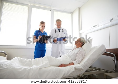 medicine, age, health care and people concept - doctor and nurse with clipboards visiting senior patient woman at hospital ward - stock photo