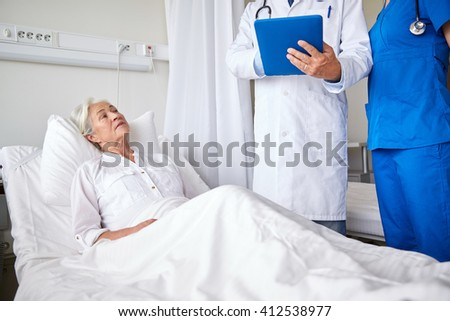 medicine, age, health care and people concept - doctor and nurse with tablet pc computer visiting senior patient woman at hospital ward - stock photo