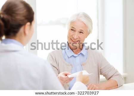 medicine, age, health care and people concept - doctor giving prescription to happy senior woman at hospital - stock photo
