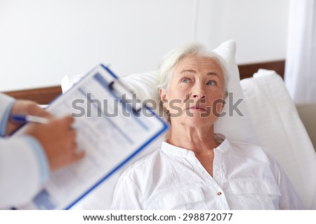 medicine, age, health care and people concept - doctor with clipboard visiting senior woman at hospital ward - stock photo