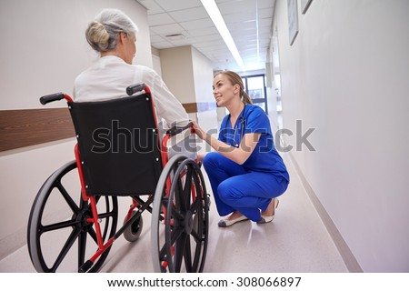 medicine, age, support, health care and people concept - happy nurse talking to senior woman patient in wheelchair at hospital corridor - stock photo