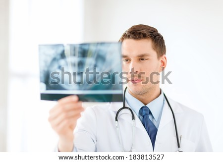 medicine and healthcare concept - concerned male doctor or dentist looking at x-ray in hospital - stock photo