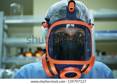 Medicine and science, and pharmaceutical laboratory with scientist wearing mask and looking at camera - stock photo