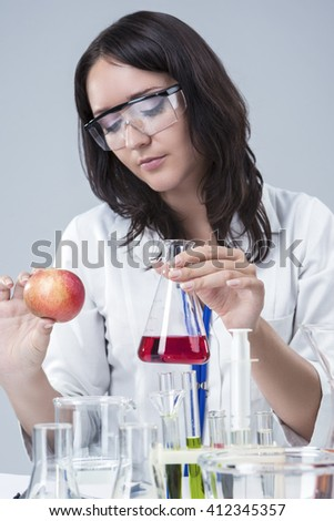 Medicine and Science Concepts and Ideas. Caucasian Female Researcher Investigating Organic Fruits in laboratory. - stock photo