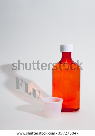 Medicine bottle with measuring cup on white background with Flu written in shadow - stock photo