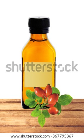 medicine bottle with yellow syrup and dog-rose on table isolated on white background - stock photo