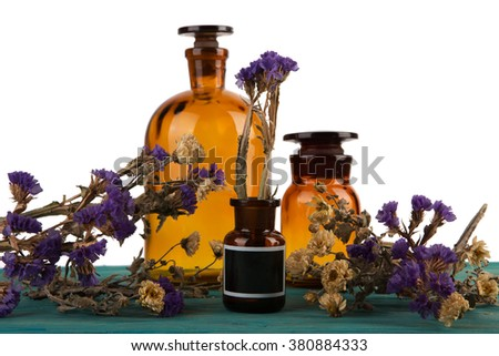 medicine bottles on wooden table isolated on blue with flower - stock photo
