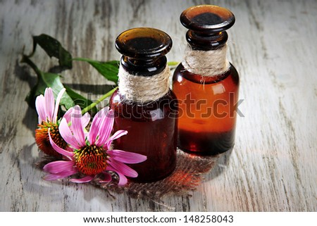 Medicine bottles with purple echinacea flowers on wooden table - stock photo