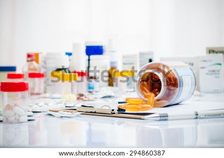 medicine capsules laid out on a folder - stock photo