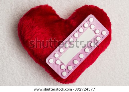 Medicine contraception love and birth control. Oral contraceptive pills on red heart shaped little pillow - stock photo