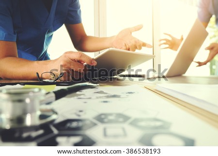Medicine doctor hand working with modern computer and digital tablet computer and medical diagram with his team on wooden desk as medical concept                                - stock photo