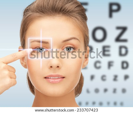 medicine, eyesight control, laser correction, people and health concept - beautiful young woman pointing finger to her eye and over blue background with eye chart - stock photo