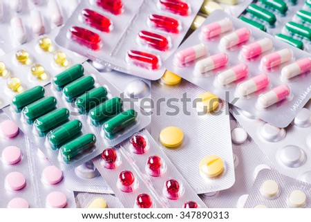 Medicine green and yellow pills or capsules on white background. Drug prescription for treatment medication. Pharmaceutical medicament, cure in container for health. Antibiotic closeup - stock photo