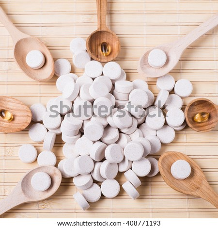 Medicine green  pills or capsules on wooden background with copy space. Drug prescription for treatment medication. Pharmaceutical medicament, cure in container for health. Antibiotic - stock photo