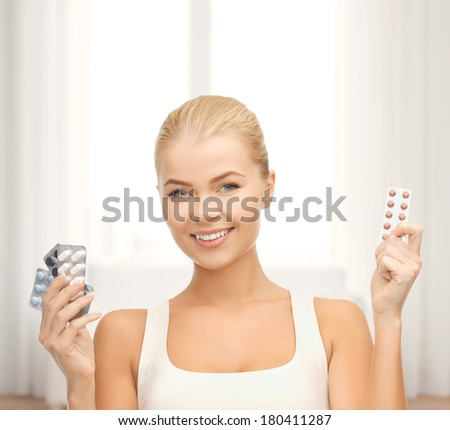 medicine, health, diet and pharmacy concept - young woman with variety of pills - stock photo