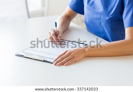medicine, people and healthcare concept - close up of female doctor or nurse writing medical report to clipboard at hospital - stock photo