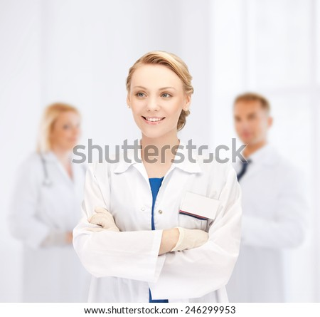 medicine, people, profession and teamwork concept - smiling young female doctor in white coat over group of medics in hospital - stock photo