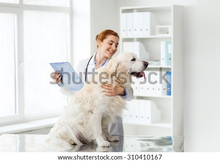 medicine, pet, animals, health care and people concept - happy veterinarian or doctor with golden retriever dog and clipboard at vet clinic - stock photo