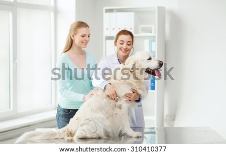 medicine, pet, animals, health care and people concept - happy woman and veterinarian doctor with stethoscope checking up golden retriever dog at vet clinic - stock photo