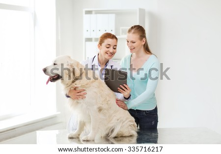 medicine, pet, health care, technology and people concept - happy woman with golden retriever dog and veterinarian doctor holding tablet pc computer at vet clinic - stock photo