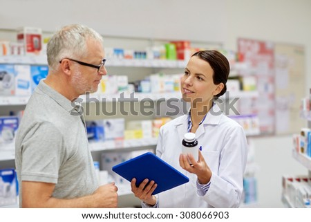 medicine, pharmaceutics, health care and people concept - happy pharmacist with tablet pc computer showing drug to senior man customer at drugstore - stock photo