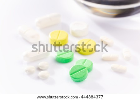 Medicine pills in various shapes, colors, and sizes on white background with selective focus on the front green pill, blur glass of water in background, back lighting to create hard long shadows - stock photo