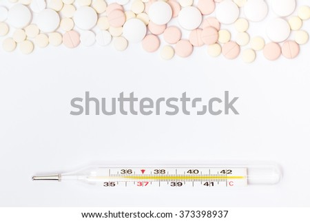 Medicine pills or capsules and thermometer on white background. Drug prescription for treatment medication. Pharmaceutical medicament, cure in container for health. Flu, temperature, ill diagnostic. - stock photo