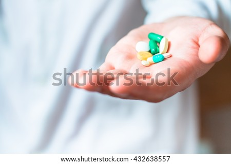 Medicine pills or capsules in hand, palm or fingers. Drug prescription for treatment medication. Pharmaceutical medicament, cure in container for health. Antibiotic, painkiller closeup. - stock photo