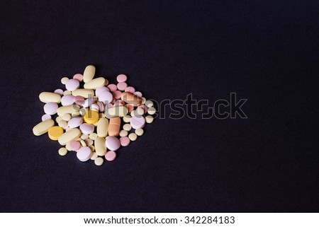 Medicine pills or capsules on black background. Drug prescription for treatment medication. Pharmaceutical medicament, cure in container for health. Antibiotic, painkiller closeup. - stock photo