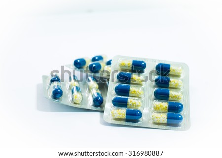 Medicine pills or capsules on white background. Drug prescription for treatment medication. Pharmaceutical medicament, cure in container for health. Antibiotic, painkiller closeup. - stock photo