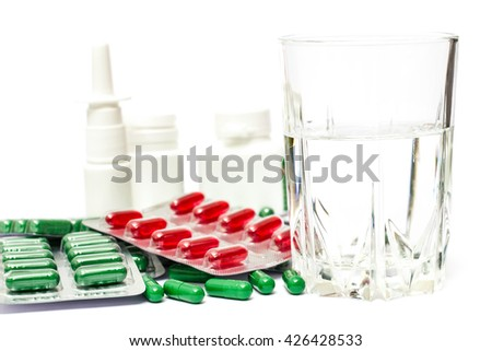 Medicine pills or capsules with glass of water on white background. Drug prescription for treatment medication. Pharmaceutical medicament, cure in container for health.  - stock photo