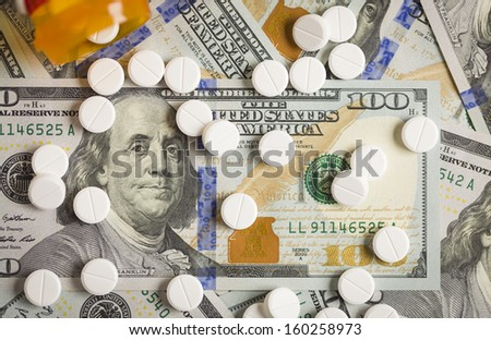 Medicine Pills Scattered on Newly Designed U.S. One Hundred Dollar Bills. - stock photo