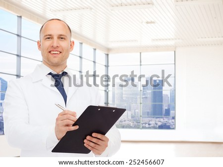 medicine, profession, people and healthcare concept - smiling male doctor with clipboard writing prescription over clinic background - stock photo