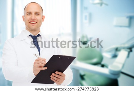 medicine, profession, stomatology and healthcare concept - smiling male dentist with clipboard writing prescription over medical office background - stock photo