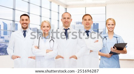 medicine, profession, teamwork and healthcare concept - group of smiling medics or doctors with clipboard and stethoscopes over clinic background - stock photo
